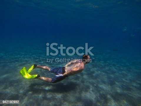 831127716 istock photo Young man diving underwater 942192932