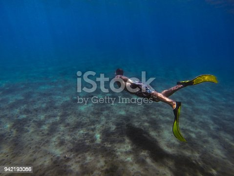 831127716 istock photo Young man diving underwater 942193086