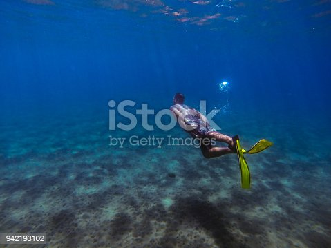 831127716 istock photo Young man diving underwater 942193102