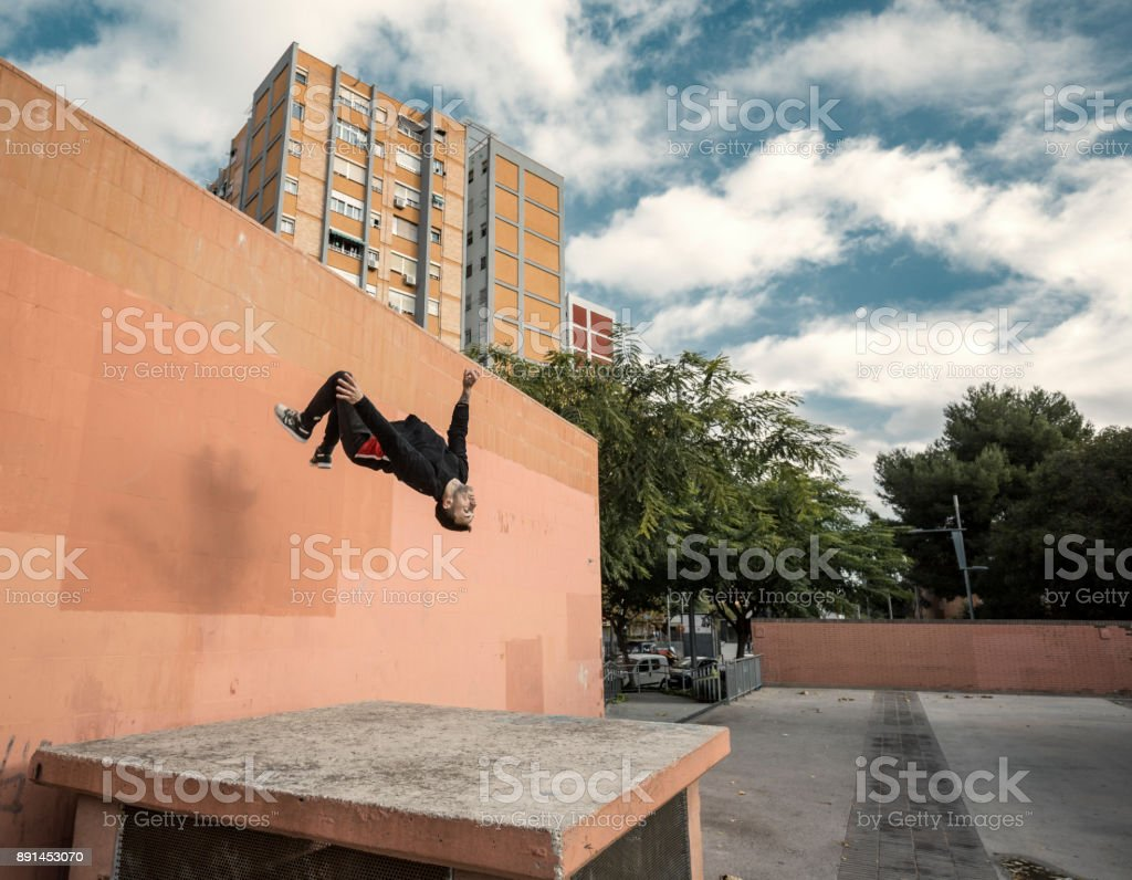 Young man doing a backflip practicing parkour in the city stock photo