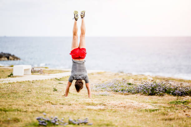 Young man doing a hand stand by the sea. stock photo