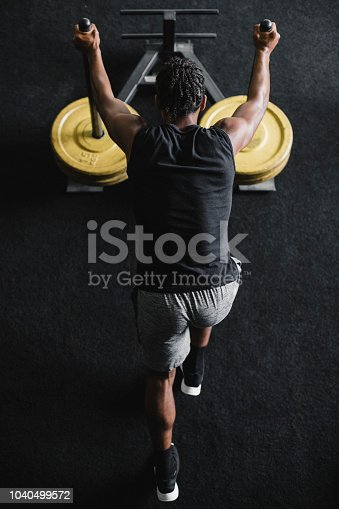 Young man doing a weighted sled exercise in the gym with his personal trainer.