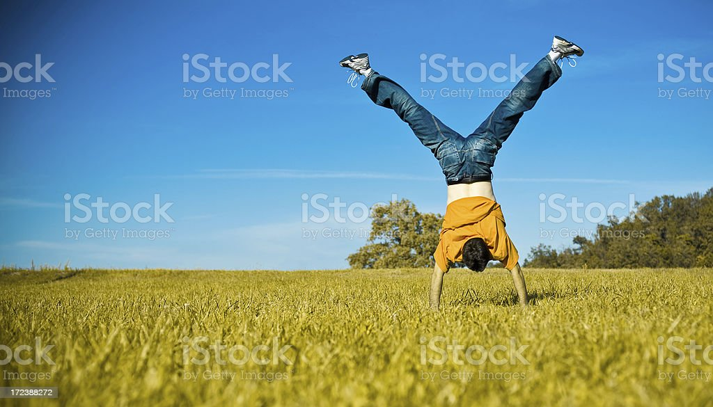 young man doing acrobatic trick in the field stock photo