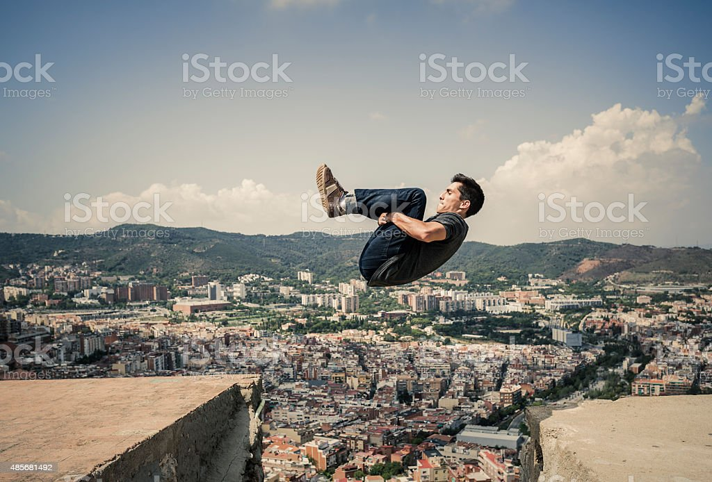 Young man doing air somersault and practicing parkour stock photo