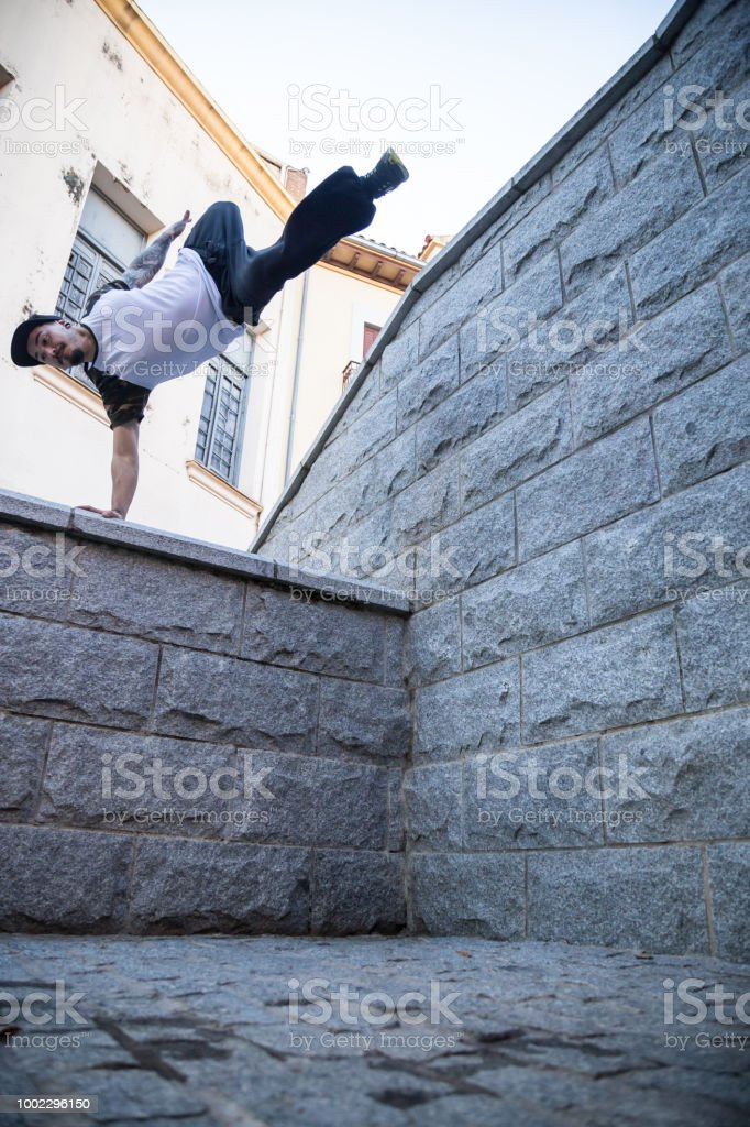 Young man doing an awesome parkour jump on the street.