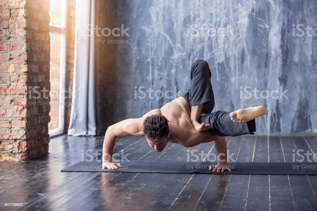 Young man doing an asana ashtavakrasana stock photo