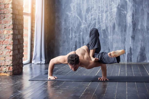 jonge man doen een asana-ashtavakrasana - extreme sporten stockfoto's en -beelden