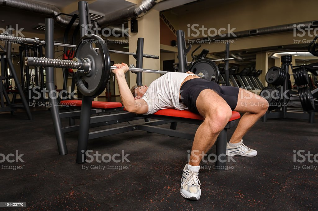 young man doing bench press workout in gym stock photo