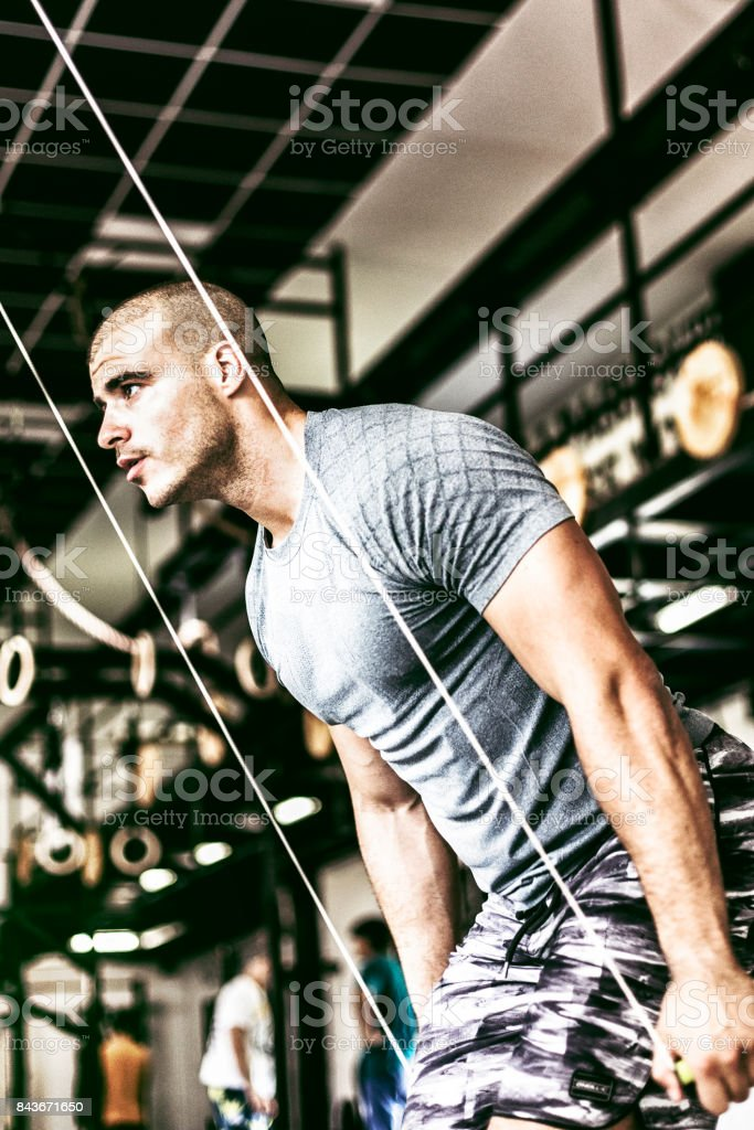 Young man doing cable fly exercise stock photo