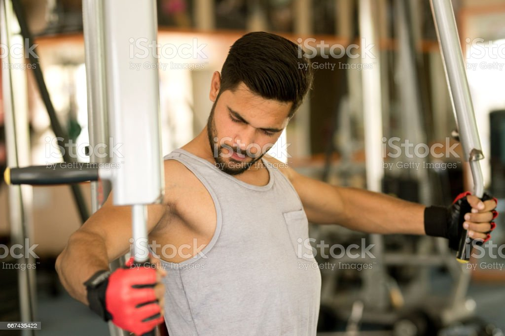Young man doing chest exercise at gym stock photo