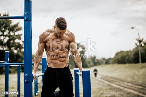 istock Young man doing dips in the local park 963355254