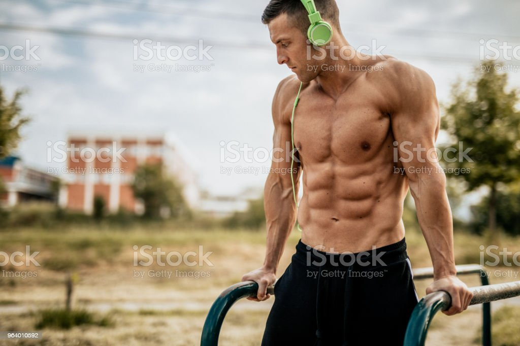 Young man doing dips in the local park - Royalty-free Abdominal Muscle Stock Photo