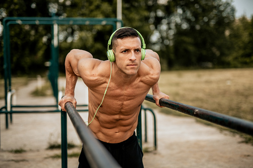 Young Man Doing Dips In The Local Park Stock Photo - Download Image Now