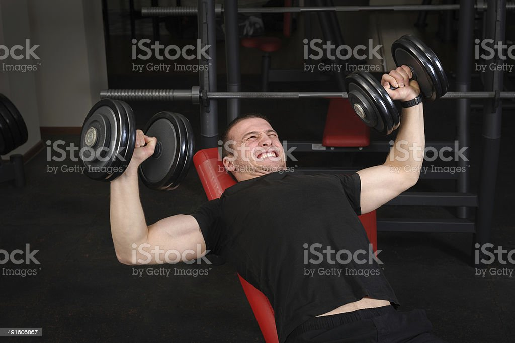 Young man doing Dumbbell Incline Bench Press workout in gym stock photo