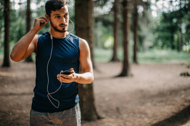 Young man doing exercise in the woods stock photo