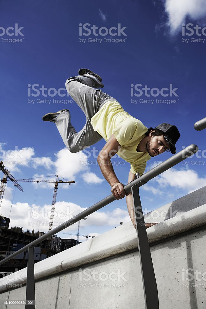 Young man doing hand stand on railing 免版稅 stock photo