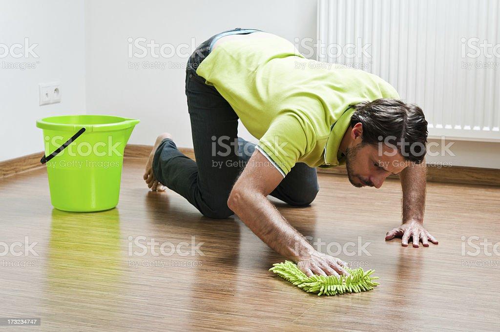 Young man doing houseworks, man is polishing the floor royalty-free stock photo