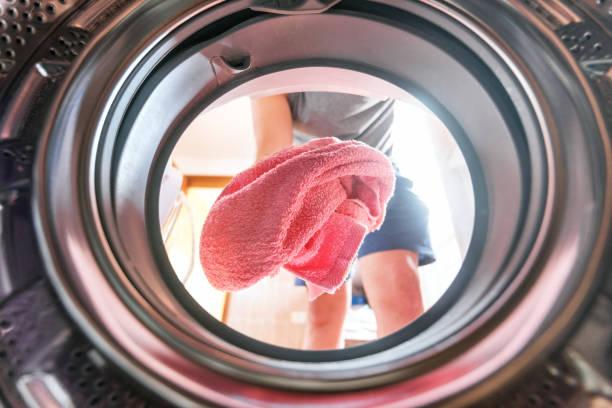 洗濯機の中からランドリー ビューをやって若い男 - 衣類乾燥機 ストックフォトと画像