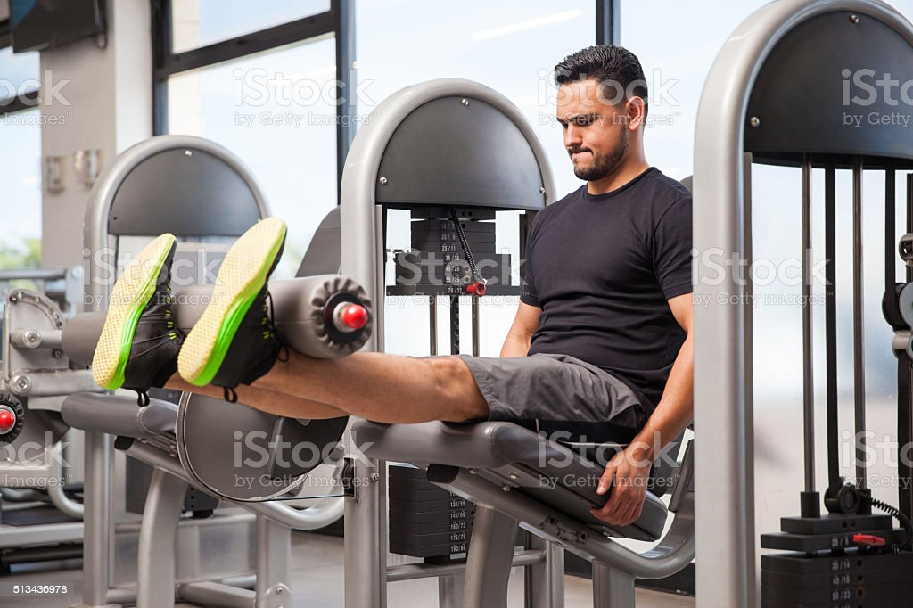 Young man doing leg extensions stock photo