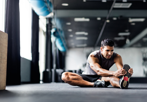 Young man doing leg stretches in the gym.