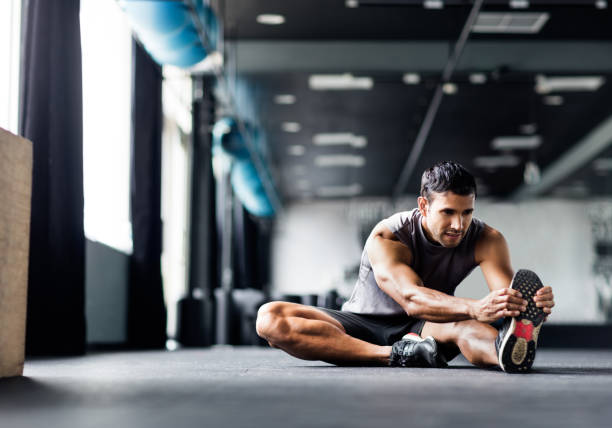 Young man doing leg stretches in the gym stock photo