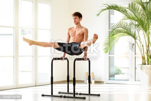Young man doing parallel bar calisthenics exercises performing a V sit with open legs in a bright high key gym with copy space and potted palm