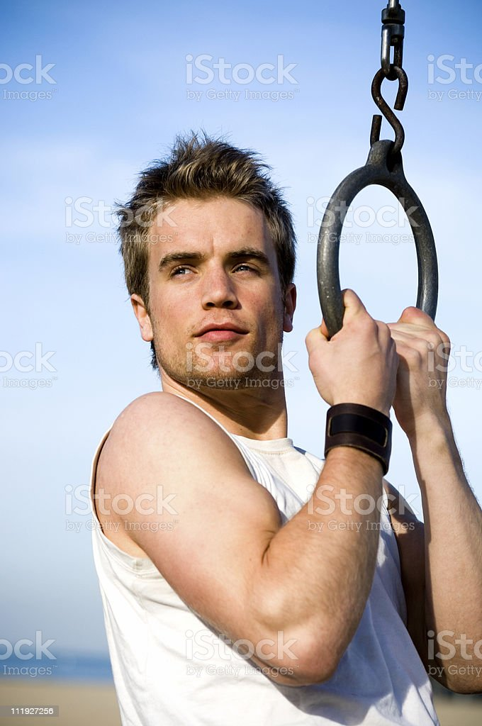 Young Man doing Pull ups on Gymnastics Ring at Beach royalty-free stock photo