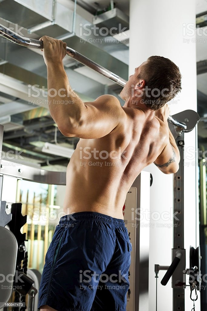 Young man doing pull-ups in gym. royalty-free stock photo