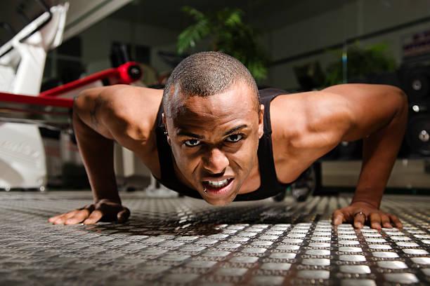 Junger Mann macht Push-ups im Fitnessstudio – Foto