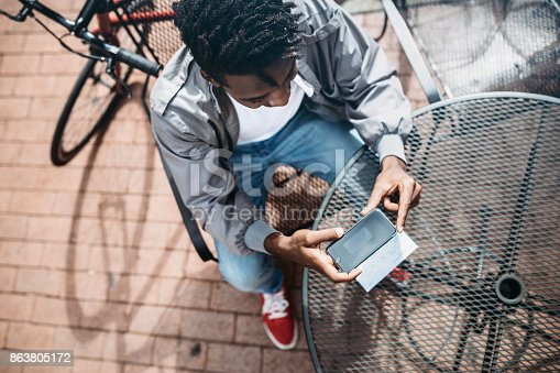 istock Young Man Doing Remote Deposit Capture of Check 863805172
