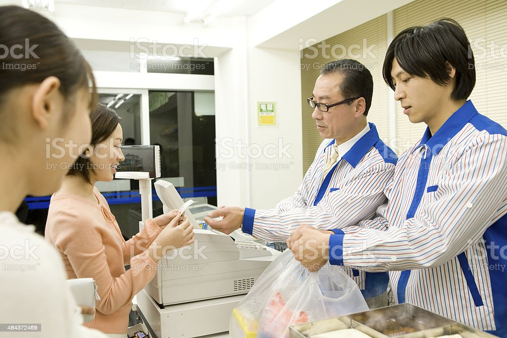 Young man doing some shopping and salesclerk at convenience store stock photo