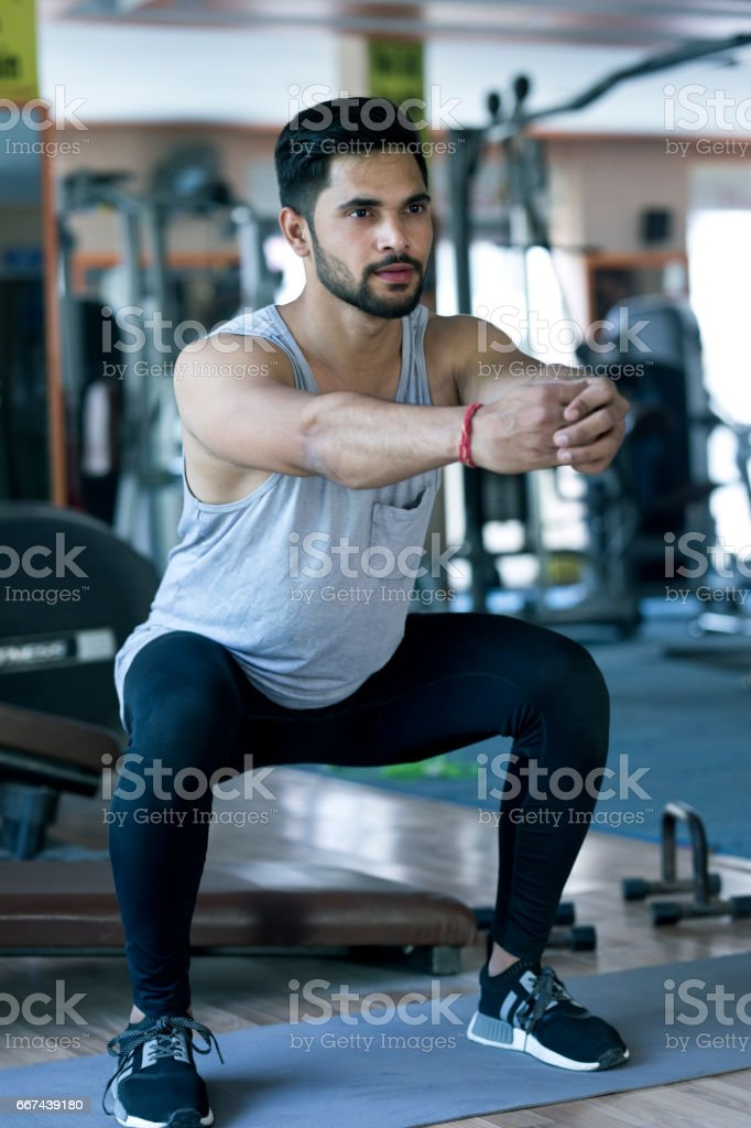 Young man doing squats stock photo