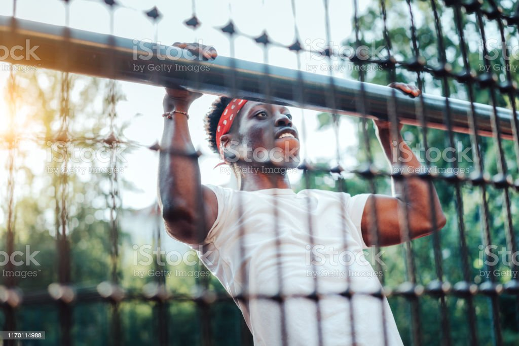 Shot of strong young african woman hanging on a pipe in sports court...
