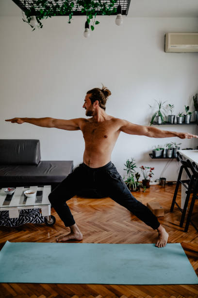 Young man doing yoga at home stock photo