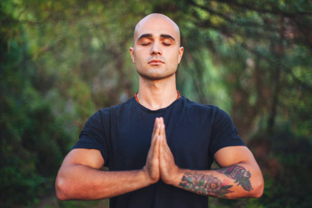 Young man doing yoga at park Confident young man doing yoga at park yoga instructor stock pictures, royalty-free photos & images