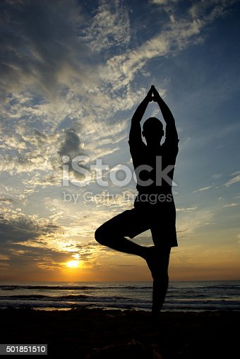 Young man doing yoga at the beach