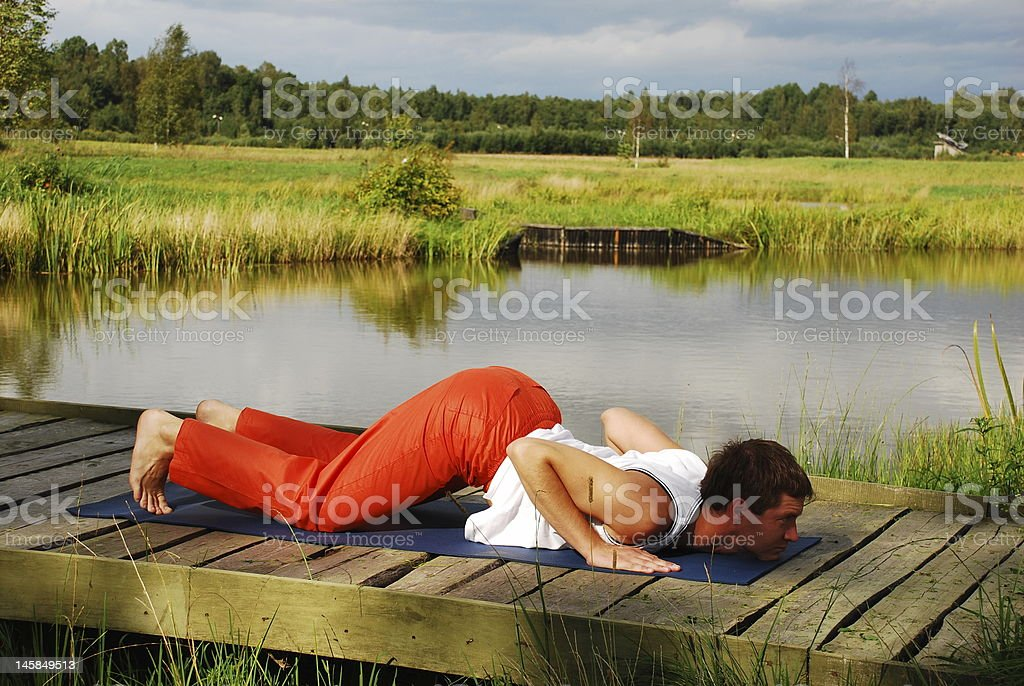 Young man doing yoga practice Surya Namaskar royalty-free stock photo