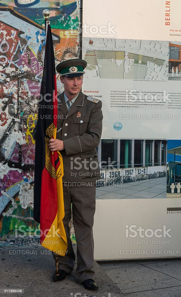 young man dressed as GDR soldier at Berlin Wall stock photo