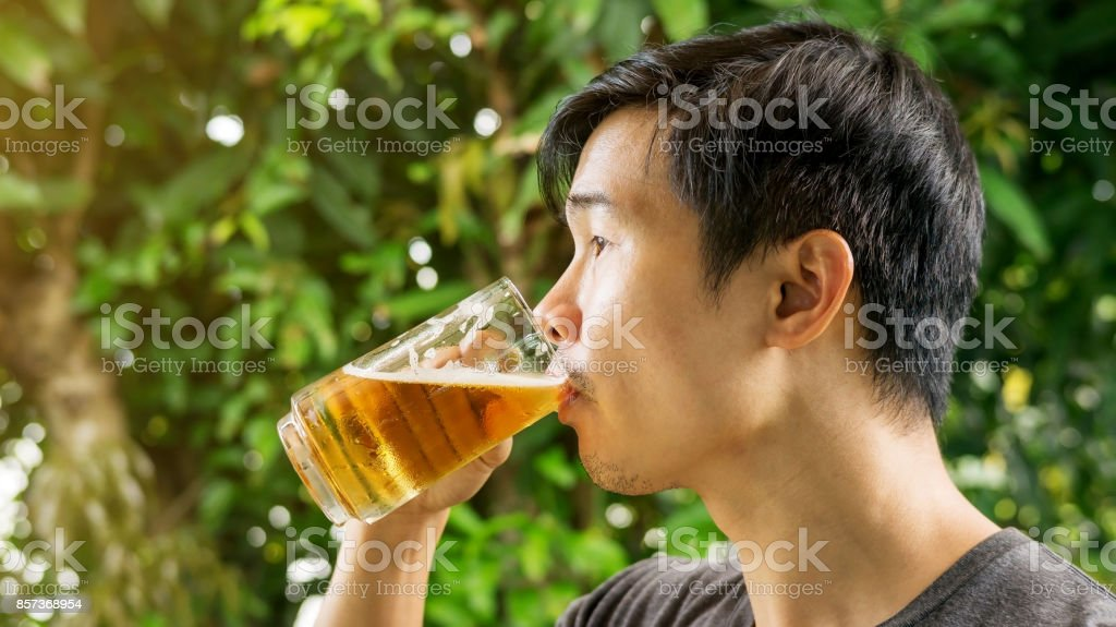 Young man drinking a beer. stock photo