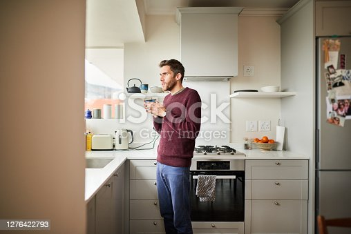 Young man deep in thought while looking out of his kitchen window over a cup of coffee