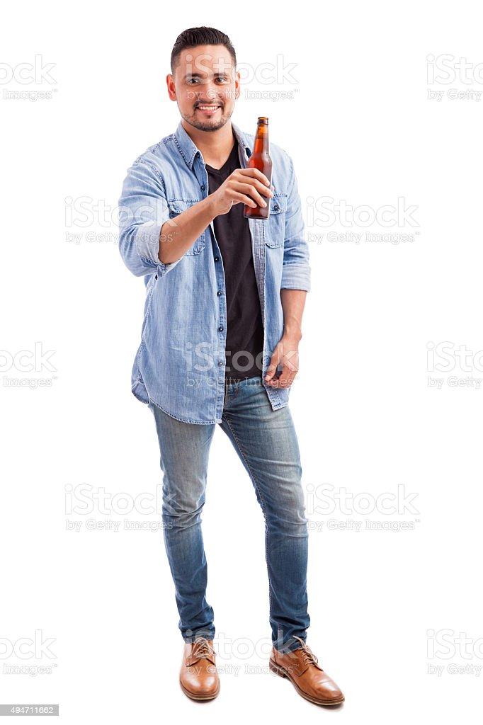 Hombre joven bebiendo cerveza desde una botella - foto de stock