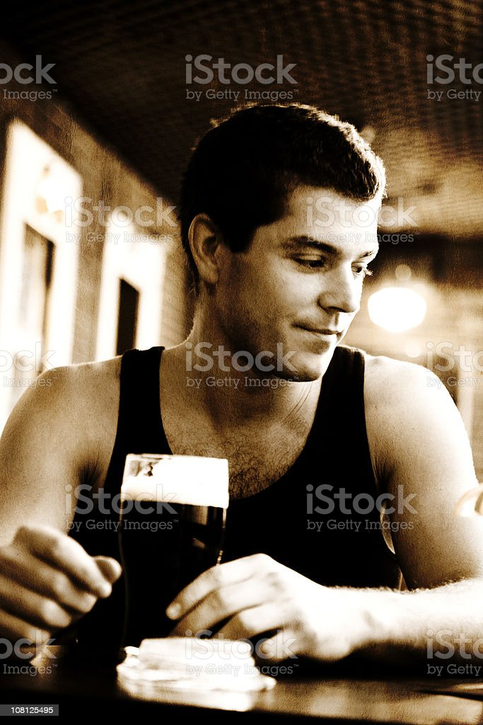Young Man Drinking Beer in Pub royalty-free stock photo