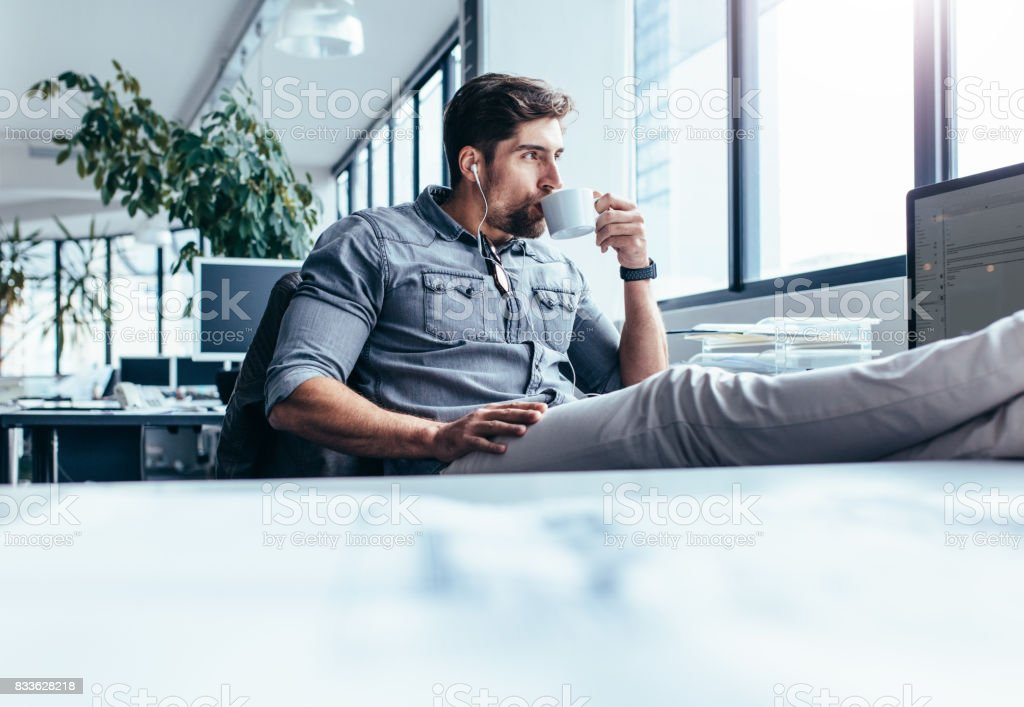 Young man drinking coffee during break in office royalty-free stock photo