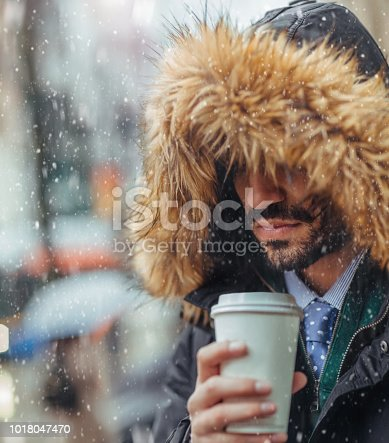 Young man drinking coffee on city street on a snowy day