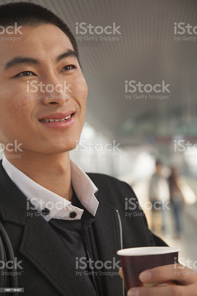 Young Man Drinking Coffee on Train Platform royalty-free stock photo