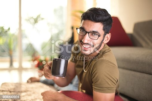Portrait of man lying on carpet and drinking coffee at home