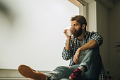 Bearded man drinking coffee by the window and looking through it. Copy space.