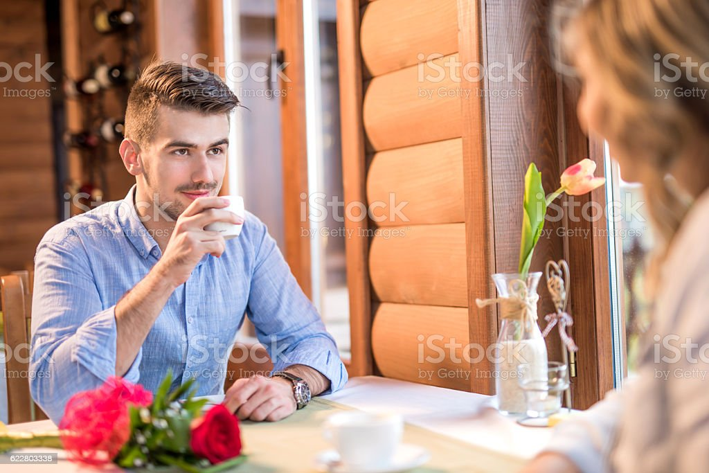 Young man drinking coffee while suducing his girlfriend stock photo