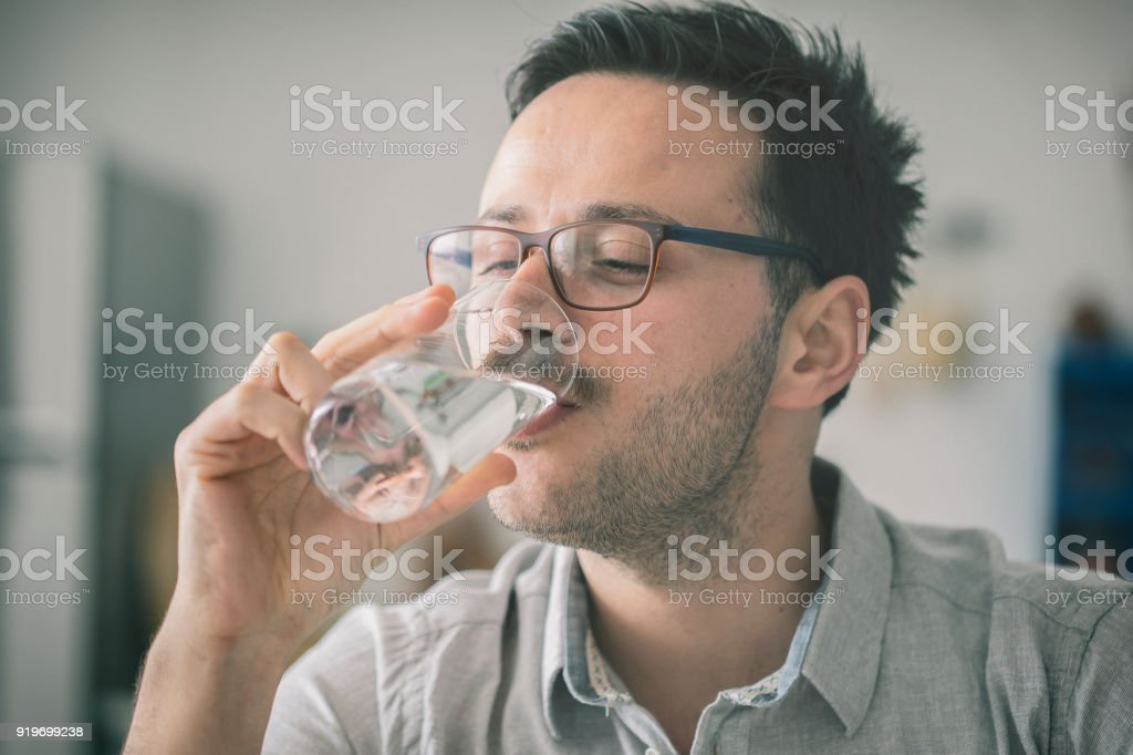 Young man drinking glass of water