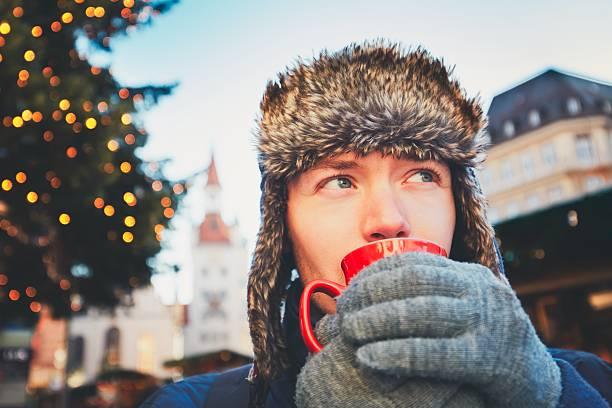 young man drinking hot wine - weihnachtsfeier münchen stock-fotos und bilder